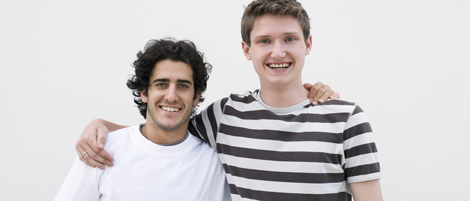 Zwei junge Männer legen sich die Hand auf die Schulter und lachen.