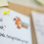 Auf einem Zettel mit dem Titel einer Session ist an einen Meta-Plan gepint.