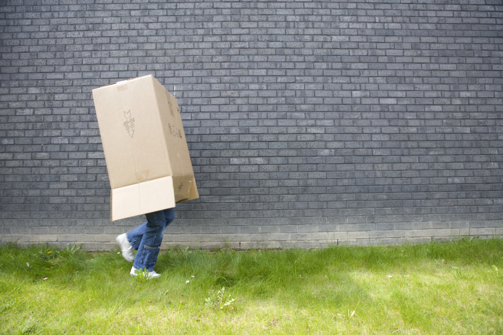 girl running away with a cardboard box over her head