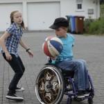 Zwei Kinder spielen mit einem Ball. Das Mädchen steht, der Junge mit dem Ball sitzt im Rollstuhl.