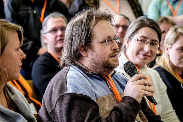Ein Mann spricht vor Teilnehmern in ein Mikrofon
