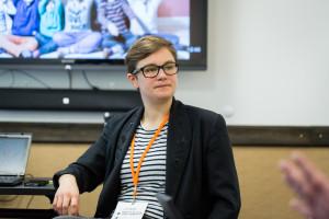 Eine junge Frau mit Kurzhaarfrisur und Brille sitze auf einem Stuhl, im Hintergrund ist ein Monitor zu sehen.