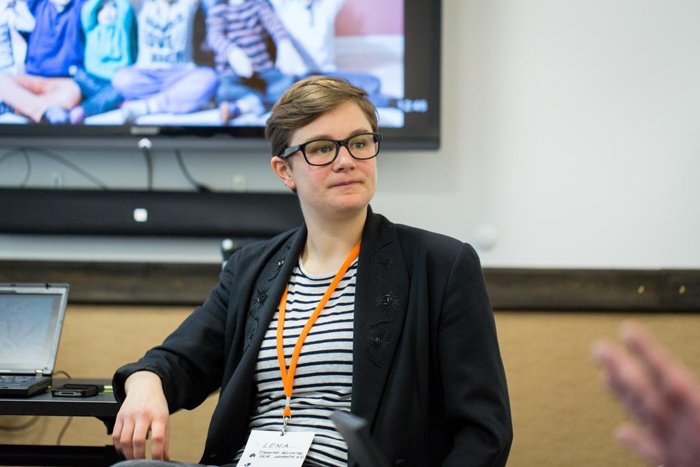 Eine junge Frau sitzt vor einem großen Flachbildschirm.