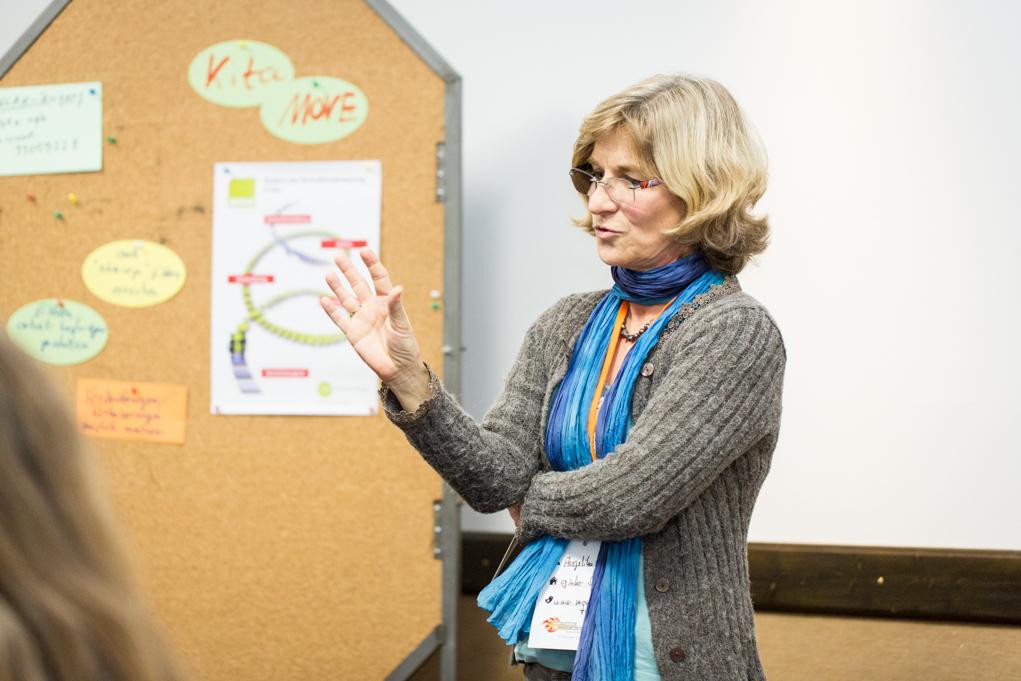 Eine blonde Frau steht vor einer Korkwand, an der bunte Zettel gepinnt sind.