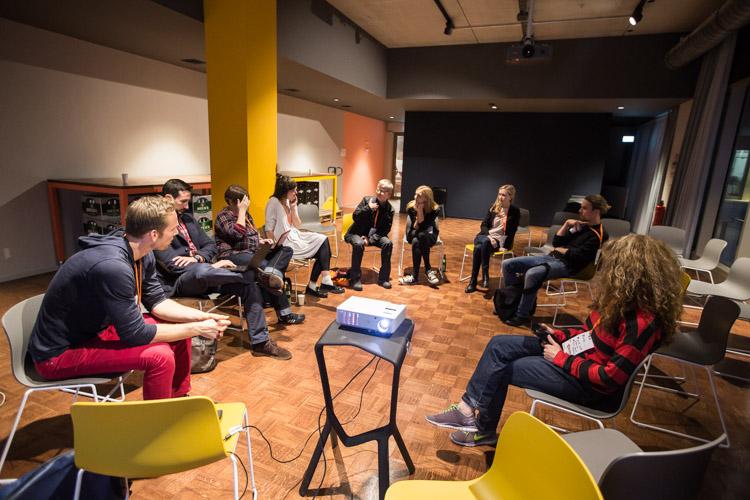 Zehn Männer und Frauen sitzen in einem Stuhlkreis.