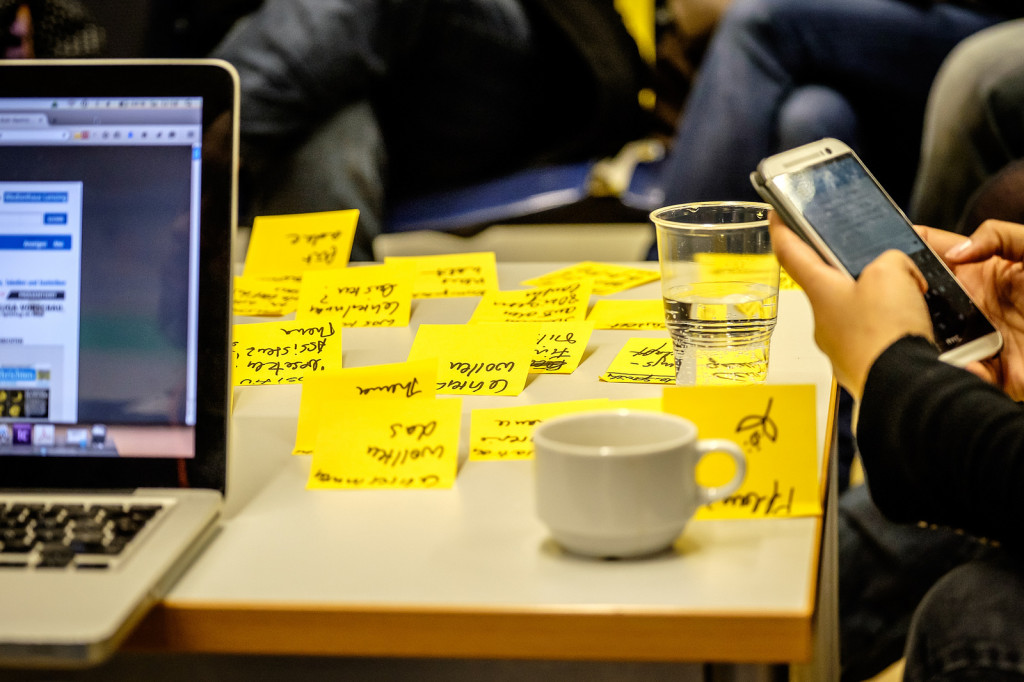 Zu sehen ist ein Tisch mit mehreren gelben Post-it-Zettel darauf, links ein Laptop, rechts eine Hand, die ein Smarphone hält.
