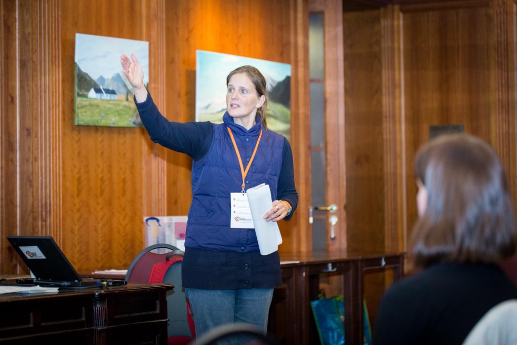 Eine Frau spricht vor einem Publikum und zeigt mit der Hand auf etwas außerhalb des Bildes.