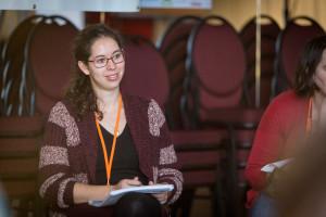 Eine Frau sitzt in einem Stuhlkreis und hält eine Mappe in der Hand.
