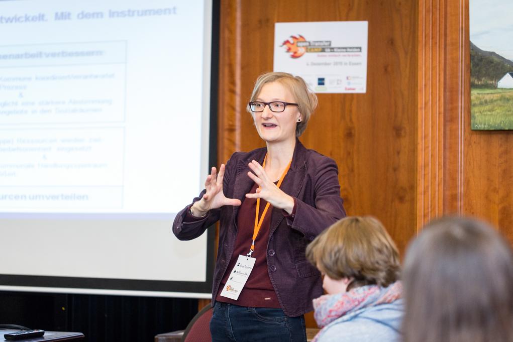 Eine blonde Frau mit Brille erklärt vor einem Zuhörerkreis etwas.