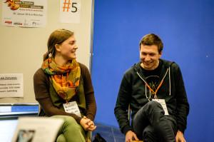 Eine junge Frau und ein junger Mann sitzen nebeneinander und lachen.