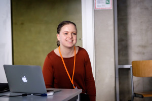 Eine junge Frau mit Laptop lächelt in die Kamera.