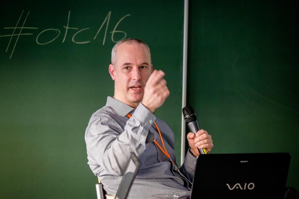 Ein Mann mit Mikrofon sitzt vor einer Tafel und gestikuliert.