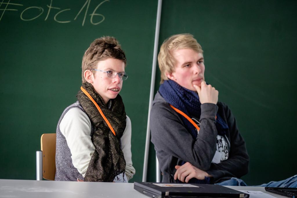Eine junge Frau und ein junger Mann sitzen vor einer Schultafel.