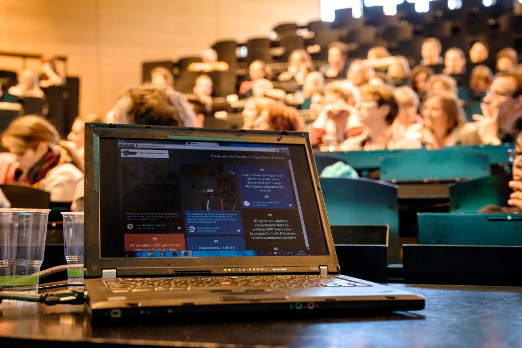 Ein Laptop steht auf einem Tisch, im Hintergrund ein Hörsaal mit vielen Menschen.