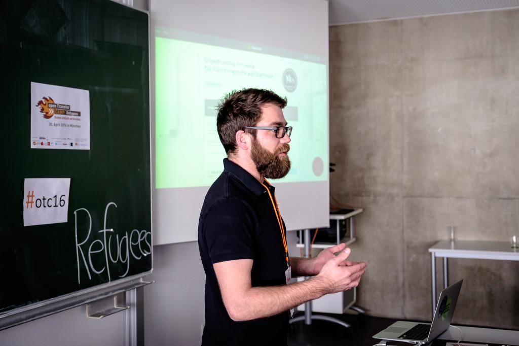 Ein junger Mann mit Bart erklärt vor einer Leinwand, auf der eine Präsentation projiziert wird, etwas.