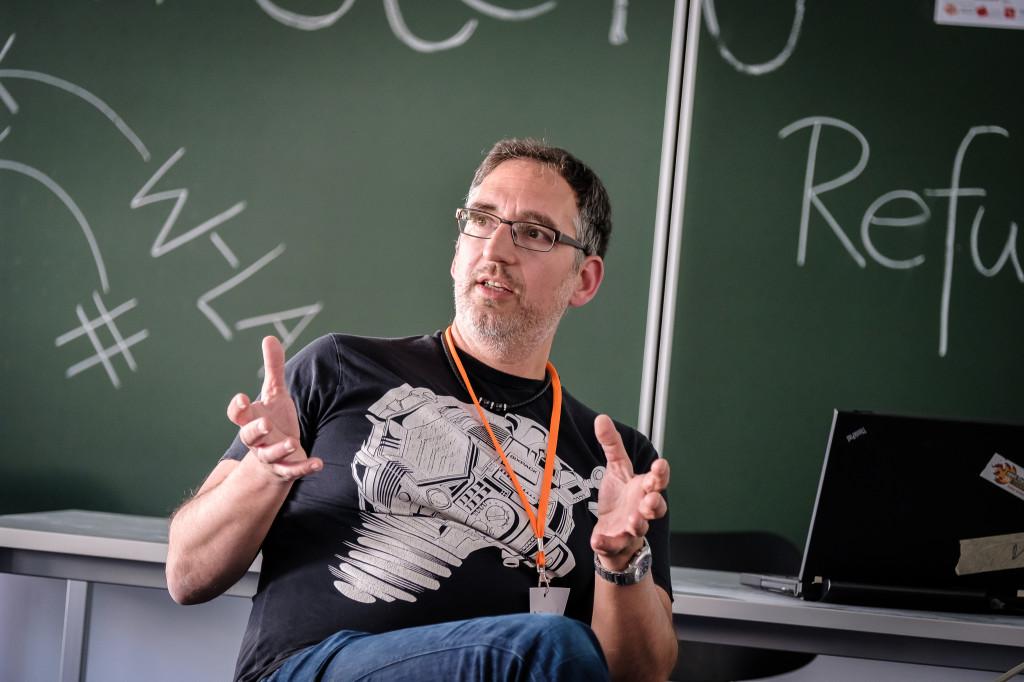 Ein Mann mit grauem Bart und Brille sitzt vor einer Schultafel und erklärt etwas.