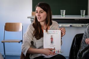 Eine junge Frau mit braunen Haaren hält ein Bilderbuch in der Hand.