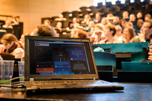 Ein Laptop steht auf einem Tisch, im Hintergrund ist ein voll besetzter Hörsaal.