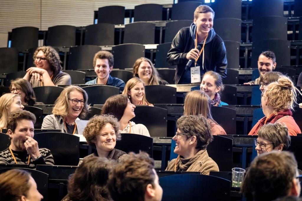 Mehrere junge Leute sitzen in einem Hörsaal und lachen.