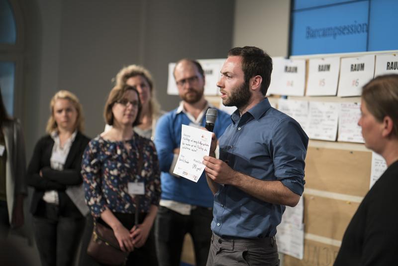 Ein junger Mann mit Mikro hält einen Zettel hoch, weitere Personen stehen im Hintergrund.