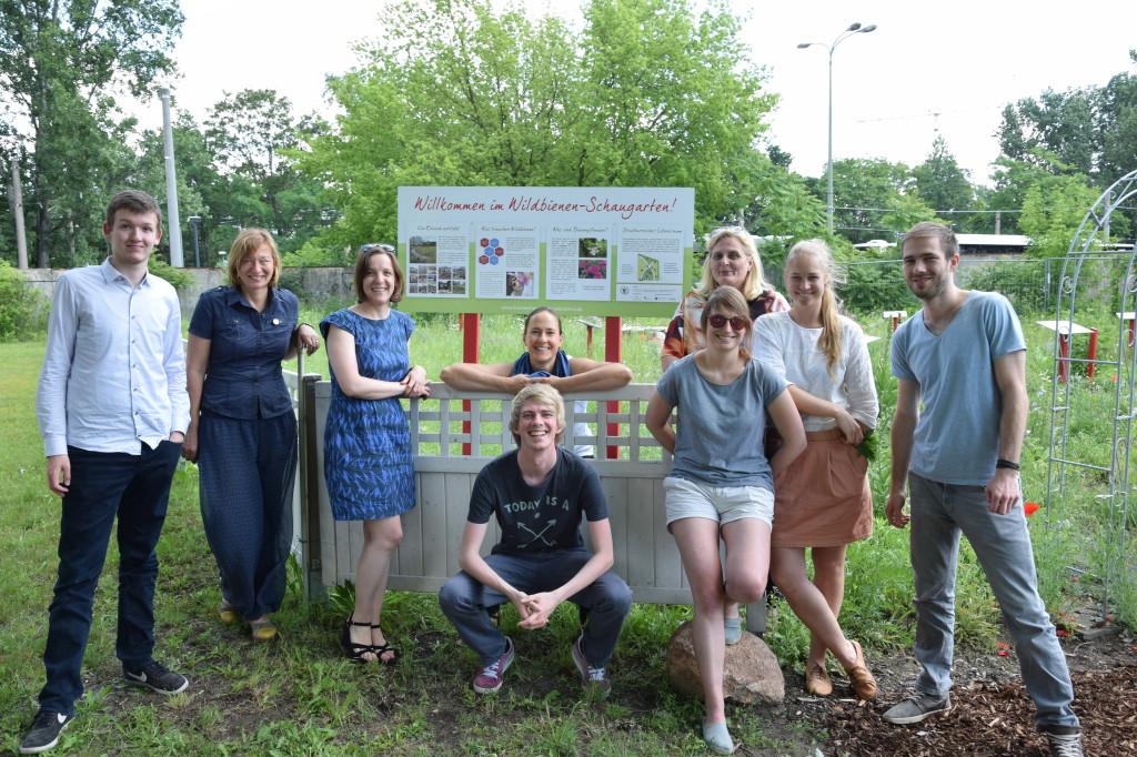 10 Männer und Frauen haben sich auf einer Rasenfläche zum Gruppenbild aufgestellt.