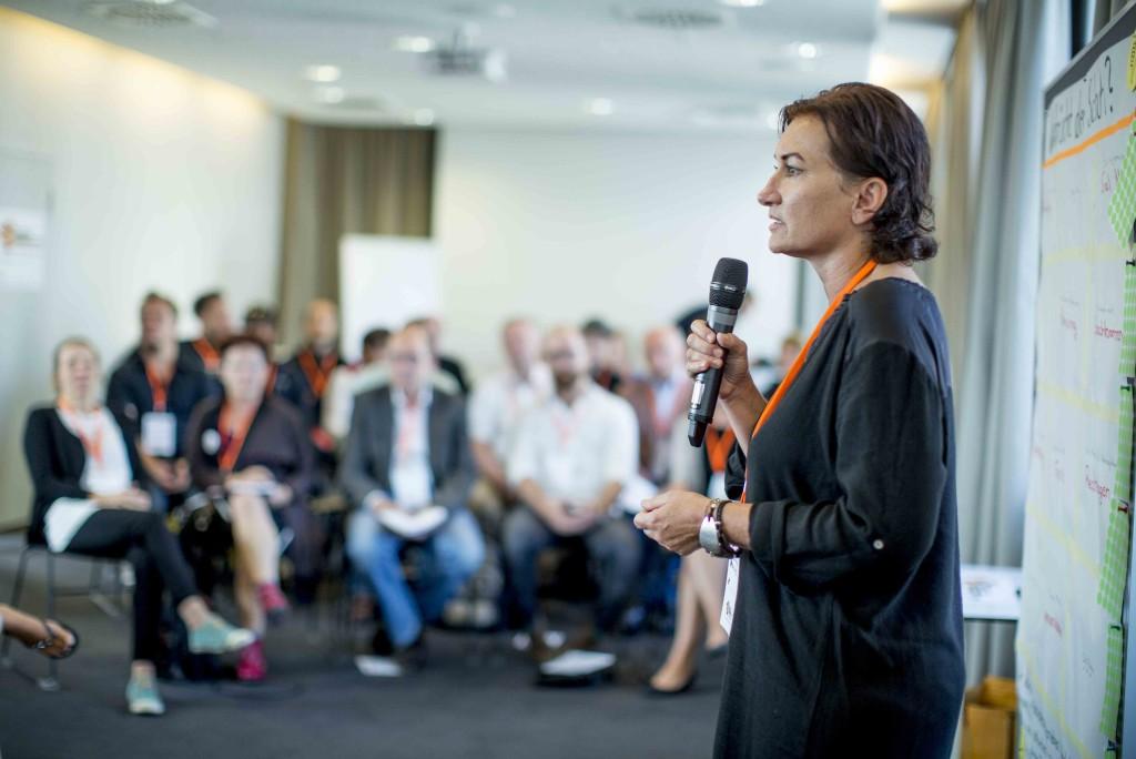 Eine Frau mit Mikrofon steht vor der sitzenden Zuhörerschaft.