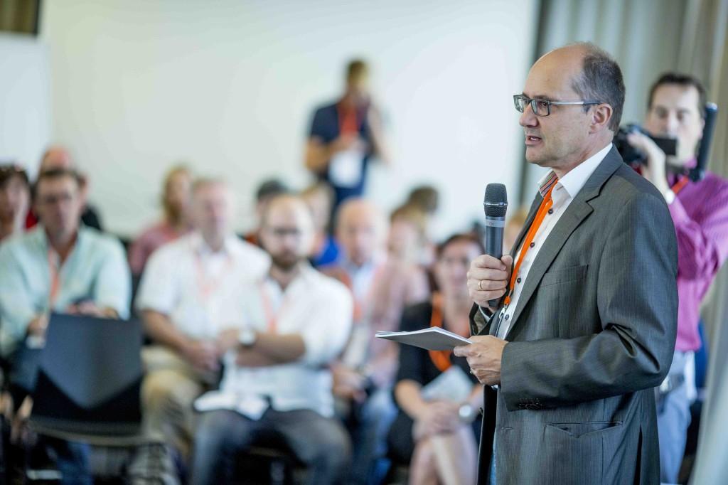 Ein Mann mit Mikrofon steht vor einer sitzenden Zuhörerschaft.