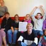 Eine Gruppe von Menschen sitzt auf einem Sofa. in der Hand hält eine Person einen Ordner auf dem draufsteht Mach Dein Projekt. Alle schauen in die Kamera.