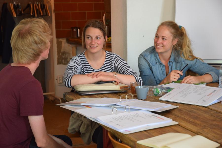 Katharina und Katrin von der Organisation Kuchentratsch tauschen sich mit Tobias von Wohn:sinn aus, den man nur von hinten sieht.