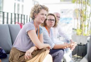 Zwei Frauen sitzen auf einer Terasse und erzählen.