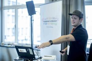 Ein junger Mann mit Basecap erläutert etwas am Laptop.