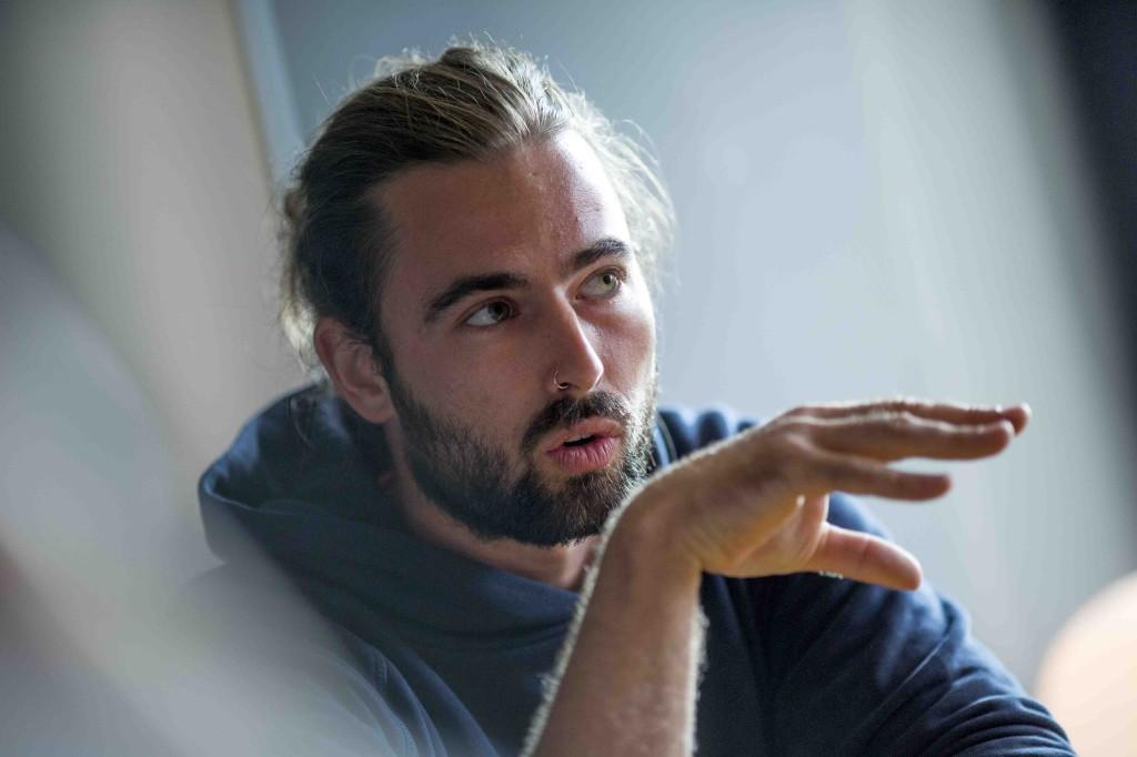 Ein junger Mann mit Bart erklärt etwas.