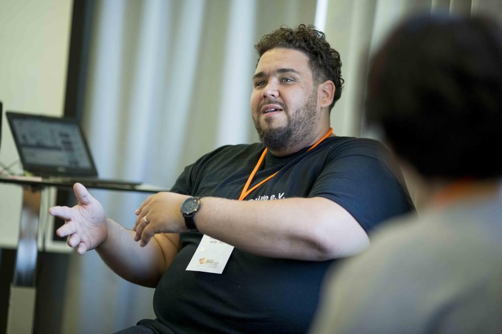 Ein junger Mann erklärt etwas vor einer kleinen Runde von Zuhörern. kleine
