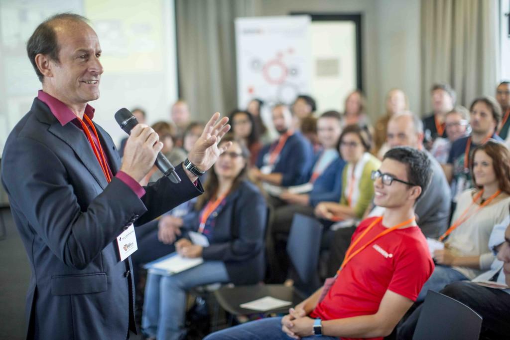 Ein Mann mit Mikrofon spricht begeistert vor einer sitzenden Zuhörerschaft.