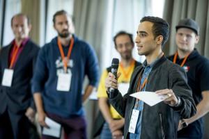 Ein junger Mann steht in einer größeren Gruppe und spricht in ein Mikrofon.