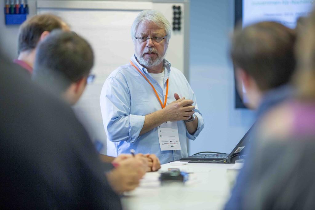 Ein Mann mit weißen Haaren steht vor einer Gruppe Zuhörer und erzählt.