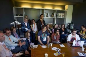 In einem Seminarraum stehen und sitzen dicht gedrängt Menschen.