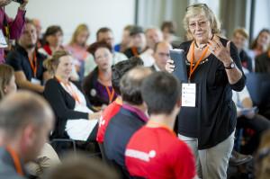 Eine ältere Frau mit Brille spricht vor einem sitzenden Publikum.
