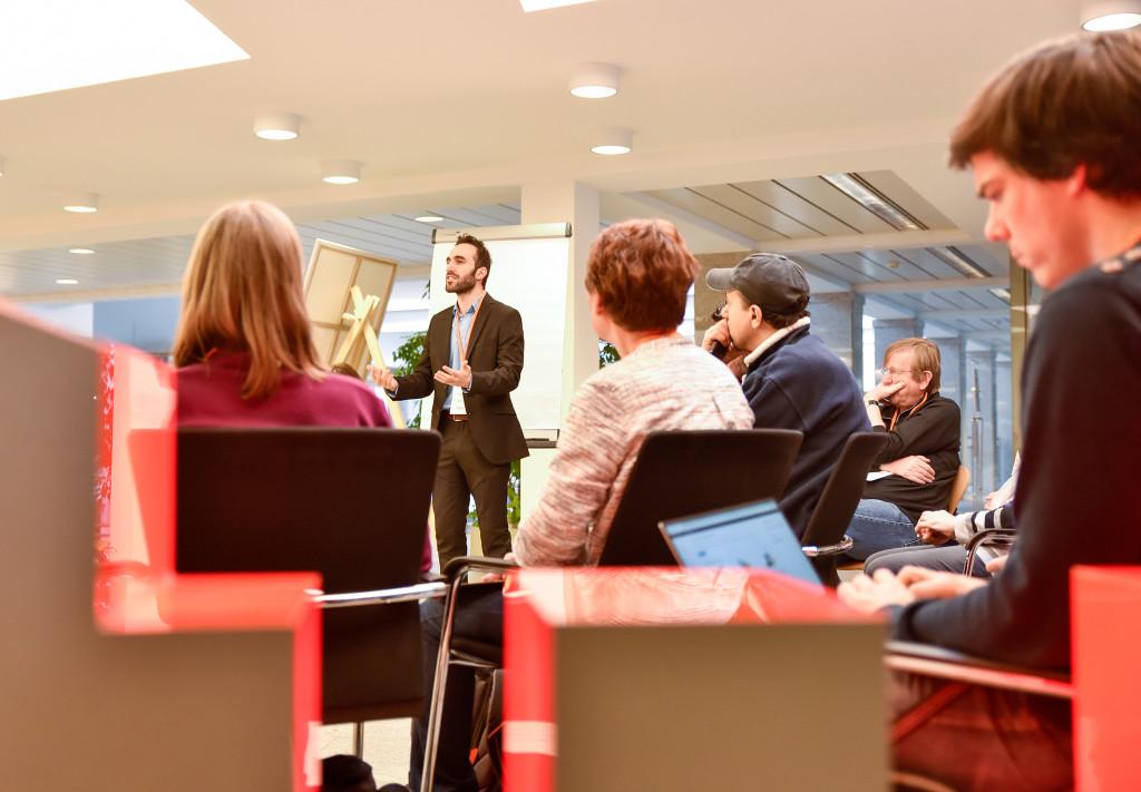 Ein Mann spricht zu einer Gruppe Menschen, die um ihn herum sitzt.