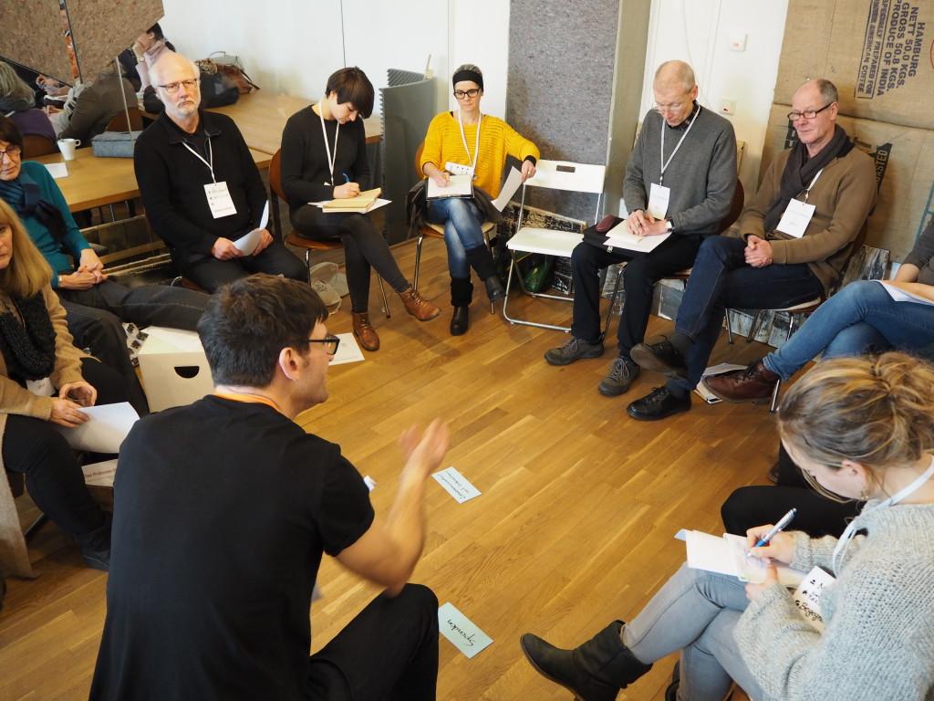 Ein Mann redet zu einer Gruppe, die im Kreis um ihn herum sitzt.
