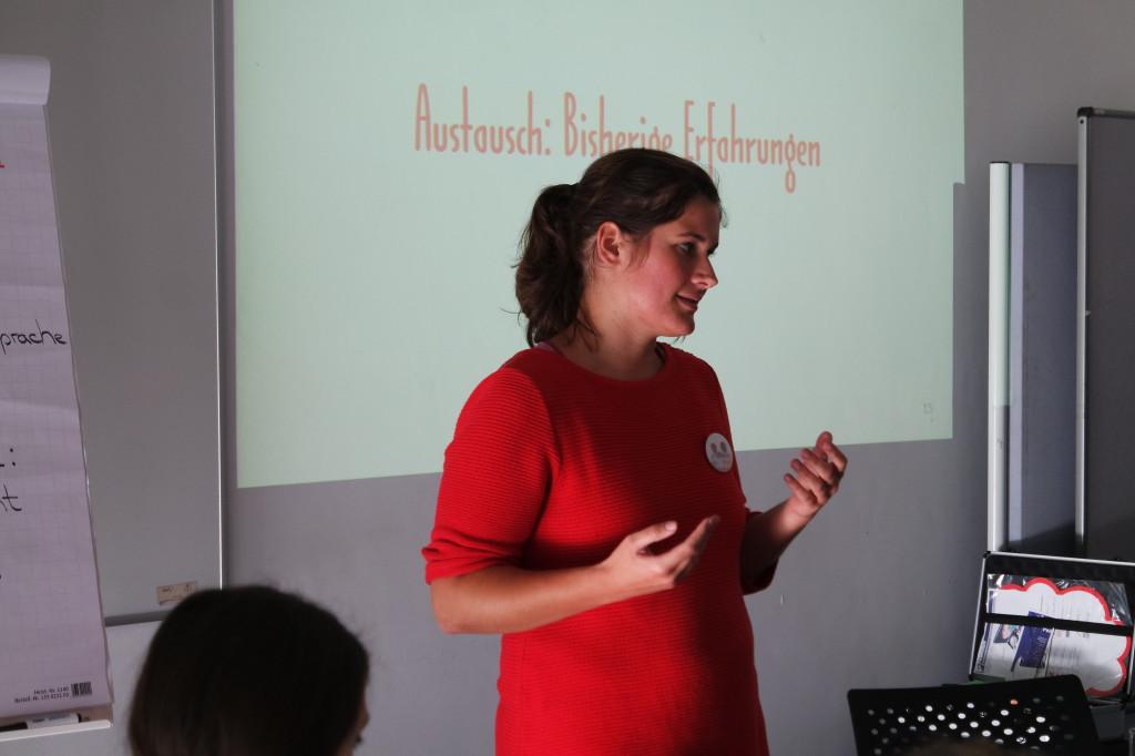 Eine Frau in rotem Kleid erklärt etwas vor einer Leinwand.