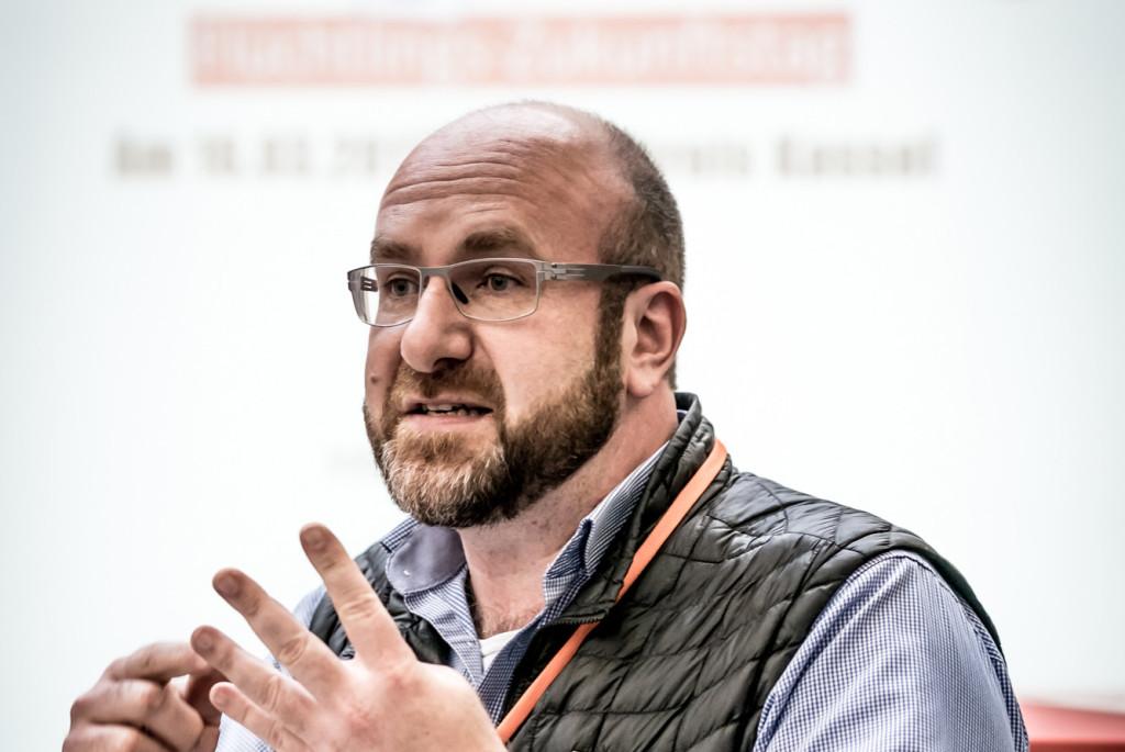 Ein Mann steht vor einer Leinwand, auf der eine Präsentation läuft.