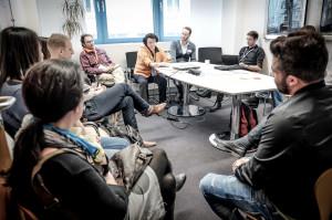 Ein dutzend Menschen sitzen in einem Konferenzraum um einen Tisch herum.