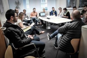 Zehn Leute sitzen in einem Konferenzraum um einen Tisch herum.