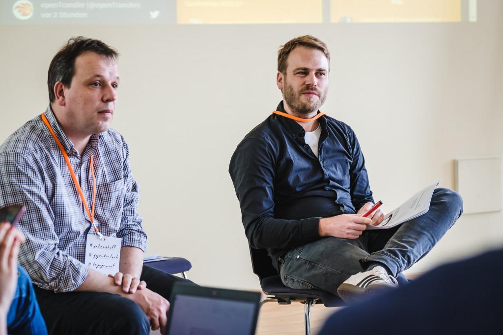 Zwei Männer sitzen in einem Stuhlkreis und sprechen.