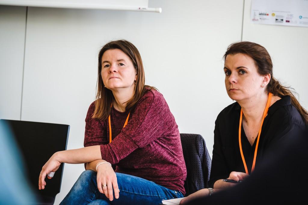 Zwei Frauen sitzen in einem Stuhlkreis und hören jemandem zu.
