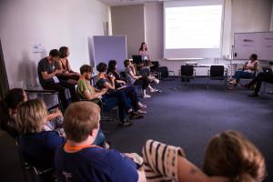 Menschen sitzen in einem Stuhlkreis und folgen einer Präsentation.