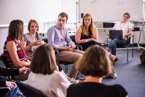 Eine Gruppe junger Menschen sitzt in einem Kreis.